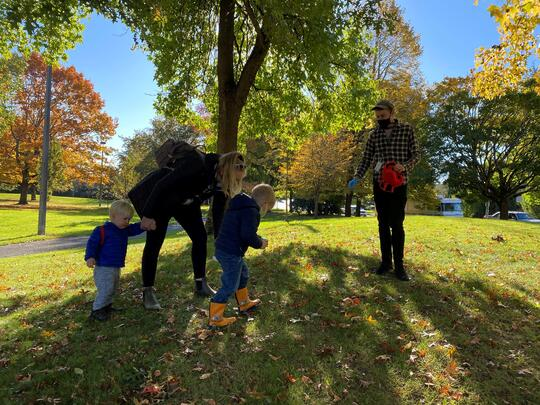 An educator works with a family on a walk at an urban park.