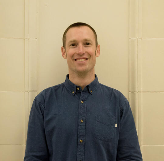 Clint Culpepper stands smiling in a navy blue button-up with a cream wall background.