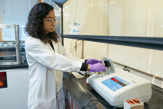 Photo in a lab setting of a woman wearing a white lab coat and purple gloves testing a water sample in lab equipment.