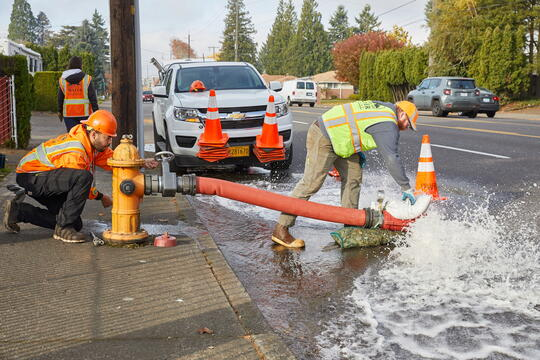 Photo of two workers wearing orange safety vests next to an orange hydrant that has a red hose connected to it and white foamy water gushing out of the hose onto the street.