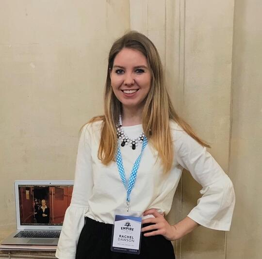 Rachel Dawson smiles with her hand on her hip, wearing a white blouse and a conference-style lanyard name tag.