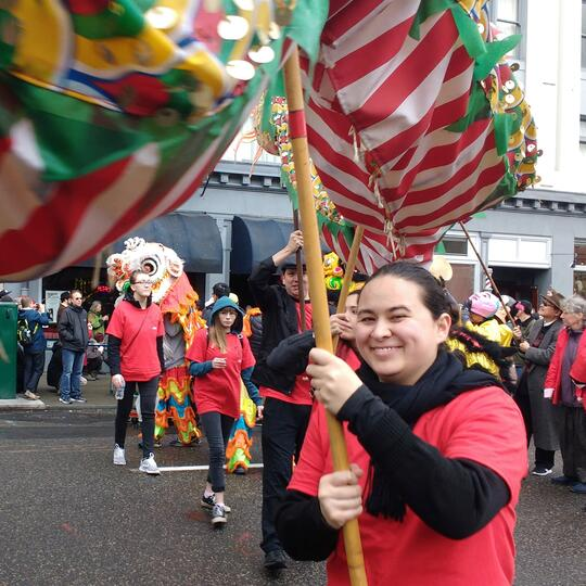 Stephanie Fong smiles while carrying a poll attached to the underbelly of a red and white-striped fabric Chinese dragon. Others behind her are also carrying polls attached to the underbelly of the latter body and tail. Stephanie and other participants are wearing red t-shirts with black long-sleeved shirts underneath. Stephanie also has a black scarf around her neck. The location appears to be in the middle of the street in Portland's Old Town, as spectators look on.