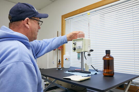 Photo of a lab setting looking over the shoulder of a water treatment operator testing a water sample on lab equipment.