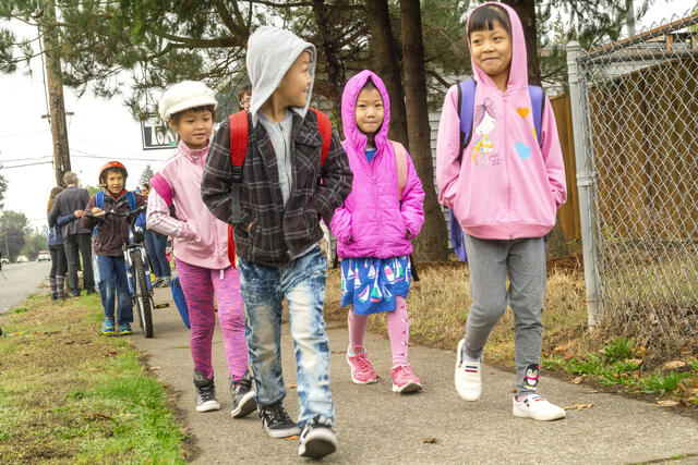 A group of students in backpacks smiling at each other as they walk two by two on a sidewalk. They all have their hands in their pockets on a chilly, October morning.