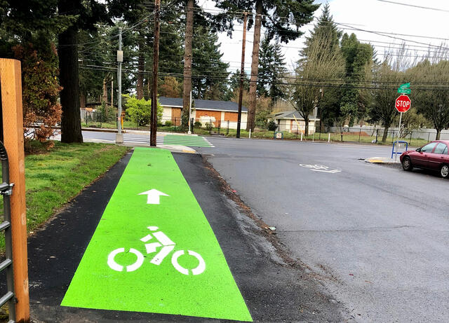 A new bicycle connection on NE Holladay as part of the HOP (Holladay, Oregon, Pacific) Neighborhood Greenway to a crossing at NE 122nd Avenue (looking east). Photo by PBOT.