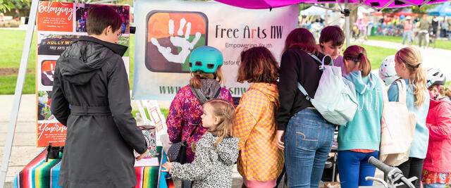Children and their parents visit Free Arts NW booth at Sunday Parkways