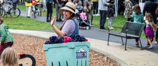 Person dressed as a box of Oregon berries waves to children