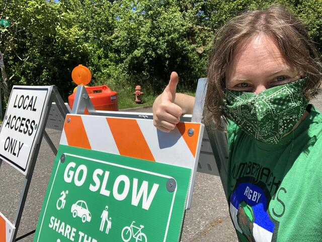 "A person kneels next to an orange and white folding traffic barricade with a ""Go Slow, Share the Road"" sign posted on it. They are wearing a green t-shirt, a green bandana face mask so you can only see their smiling eyes. They are giving a thumbs up sign."