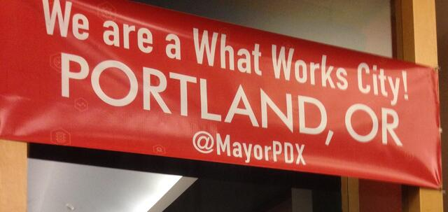 "A red banner reads ""We are a What Works City! Portland, OR @MayorPDX"""