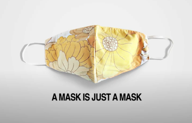 "A yellow floral mask against a white background. Black text reads ""A Mask is Just a Mask"""