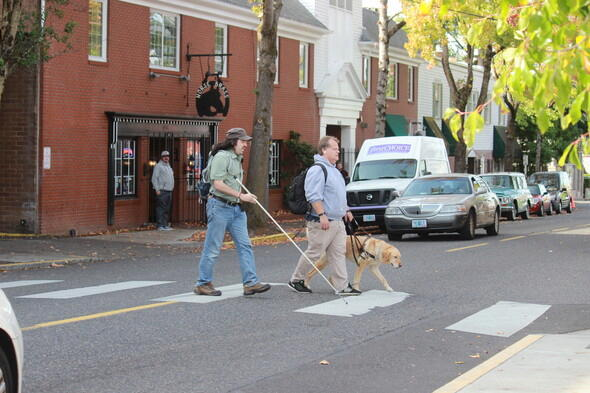 Two Portlanders, one with a white cane and one with a seeing eye dog, cross SE Belmont Street. Photo by PBOT.