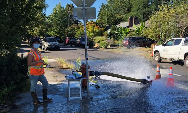 Photo of a Water Bureau employee wearing a construction vest, waterproof boots, and a face mask, facing the camera. A few feet away, a 10-foot hose attached to a hydrant spews water into the street.