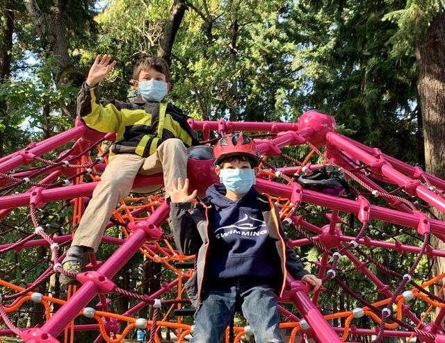 Children wearing face coverings enjoy the new Creston Park playground climbing feature, waving to the camera.
